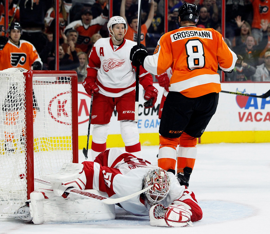 . Detroit Red Wings\' Jonas Gustavsson (50), bottom, sprawls on the ice after failing to stop the shot by Philadelphia Flyers\' Nicklas Grossman (8), right, during the second period of an NHL hockey game Saturday, Oct. 25, 2014, in Philadelphia. (AP Photo/Tom Mihalek)