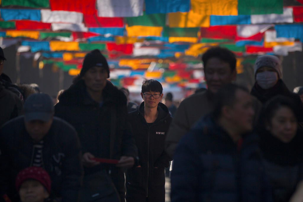 . People walk under rows of Tibetan prayer flags on the first day of the Lunar New Year at the Lama Temple in Beijing, Friday, Feb. 16, 2018. Chinese around the world celebrated the arrival of the Year of the Dog on Friday with family reunions, firecrackers and traditional food. (AP Photo/Mark Schiefelbein)
