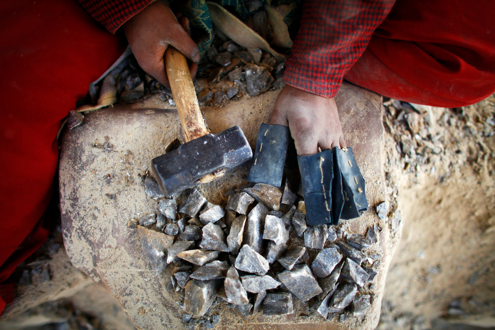 Description of . In this Friday, March 7, 2014 photo, a Nepalese woman works at a stone quarry on the eve of International Women's Day in Katmandu, Nepal. (AP Photo/Niranjan Shrestha)