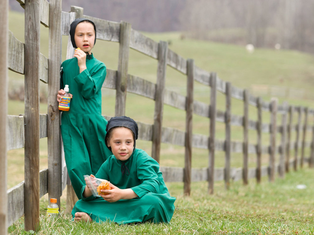 Description of . Amish girls eat snacks during an end of the school year celebration in Bergholz, Ohio on Tuesday, April 9, 2013.  (AP Photo/Scott R. Galvin)
