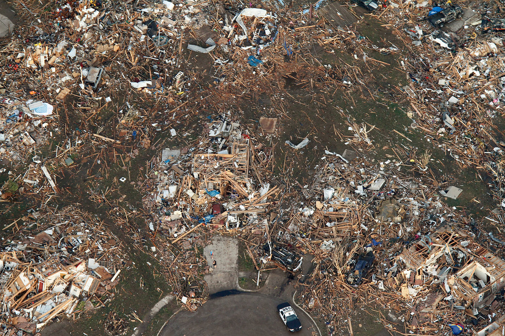 . This aerial photo shows the remains of homes hit by a massive tornado in Moore, Okla., Monday May 20, 2013. A tornado roared through the Oklahoma City suburbs Monday, flattening entire neighborhoods, setting buildings on fire and landing a direct blow on an elementary school. (AP Photo/Steve Gooch)
