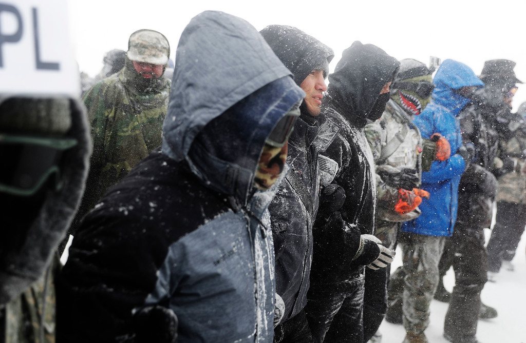 . A security line moves with a march of military veterans and tribal elders outside the Oceti Sakowin camp where people have gathered to protest the Dakota Access oil pipeline in Cannon Ball, N.D., Monday, Dec. 5, 2016. (AP Photo/David Goldman)