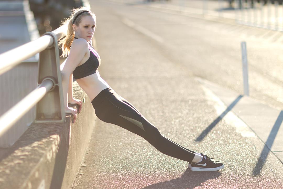 fitness model in dusk light on bridge