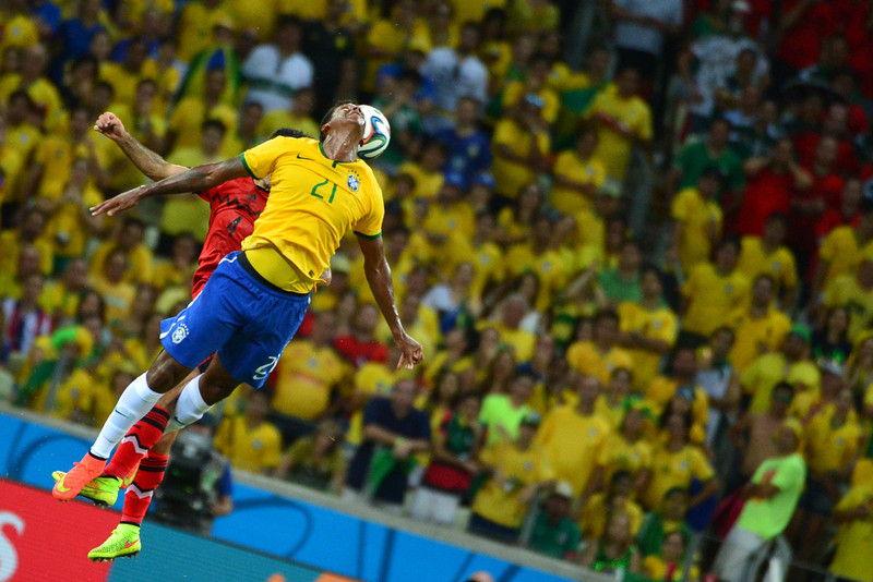 . Mexico\'s defender Rafael Marquez (L) and Brazil\'s forward Jo (R) jump for the ball during a Group A football match between Brazil and Mexico in the Castelao Stadium in Fortaleza during the 2014 FIFA World Cup on June 17, 2014. (YURI CORTEZ/AFP/Getty Images)
