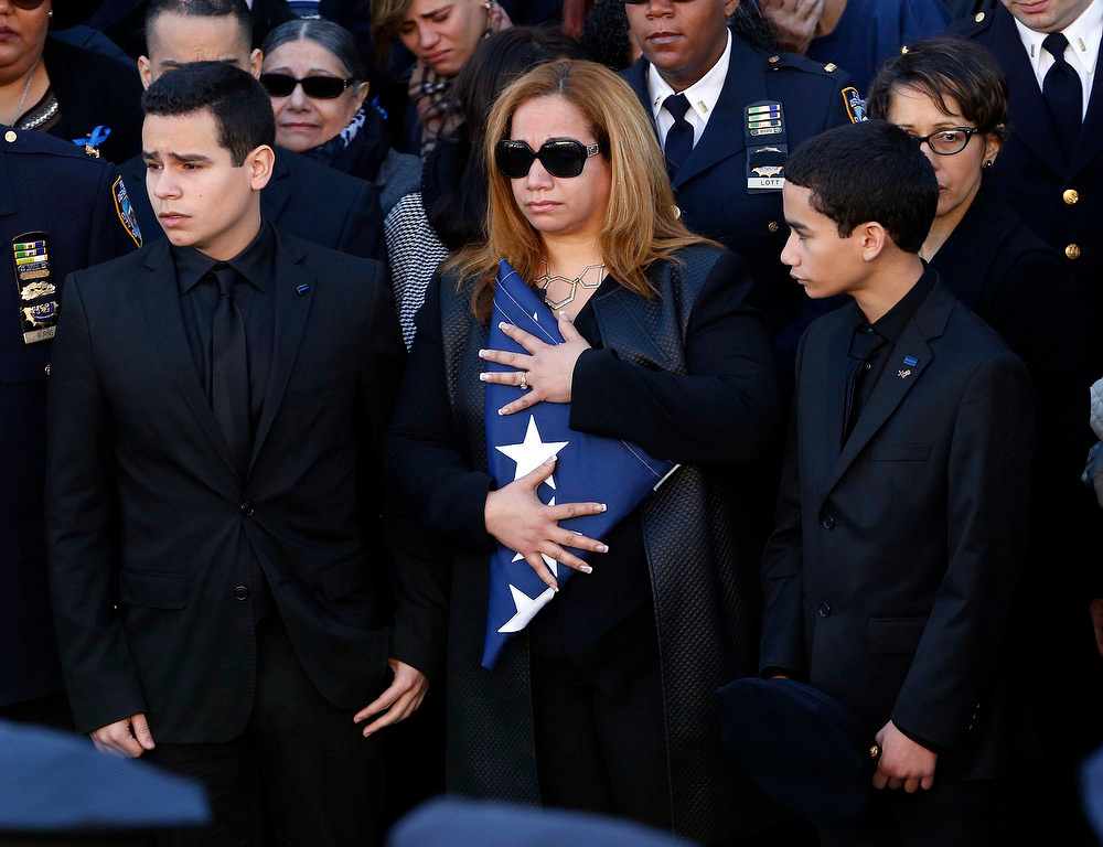 . Maritza Ramos, center, widow of New York City police officer Rafael Ramos, holds a flag while standing with her two sons, Justin Ramos, left, and Jaden Ramos, following funeral services for officer Ramos at Christ Tabernacle Church, in the Glendale section of Queens, Saturday, Dec. 27, 2014, in New York. Ramos and his partner, officer Wenjian Liu, were killed Dec. 20 as they sat in their patrol car on a Brooklyn street. The shooter, Ismaaiyl Brinsley, later killed himself. (AP Photo/Julio Cortez)