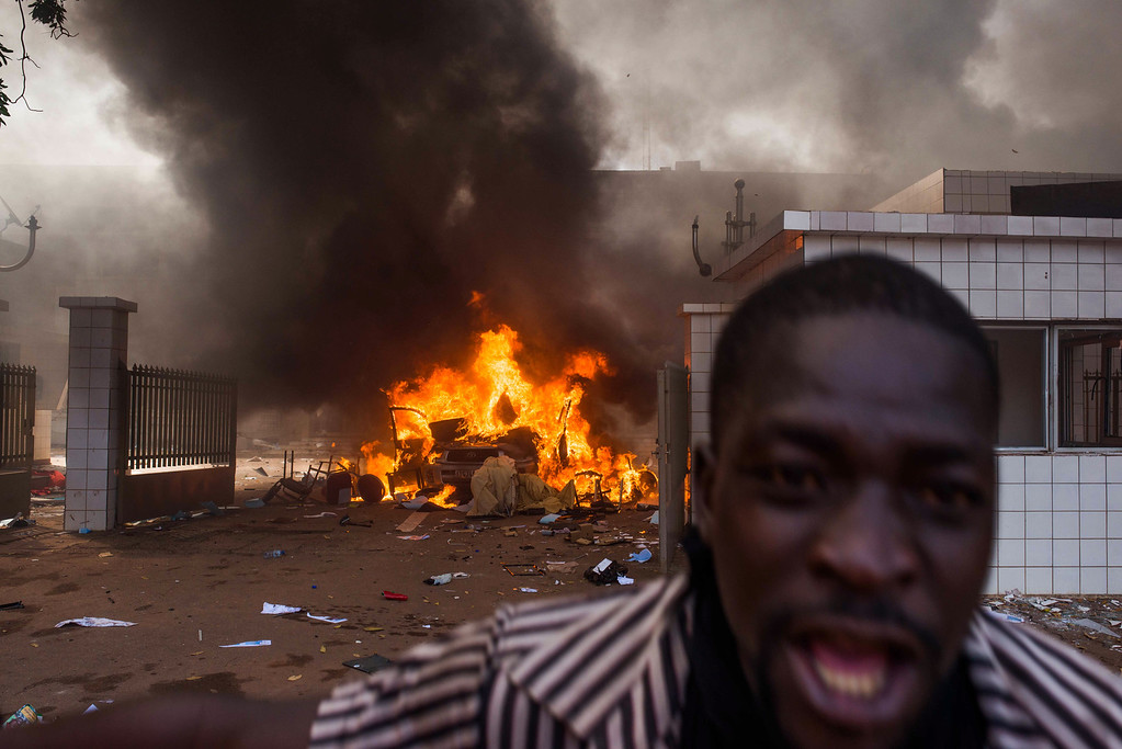 . A car burns outside the parliament building in Burkina Faso as people protest  against their longtime president  Blaise Compaore who is  seeking another term in Ouagadougou, Burkina Faso, Thursday, Oct. 30, 2014. (AP Photo/Theo Renaut)