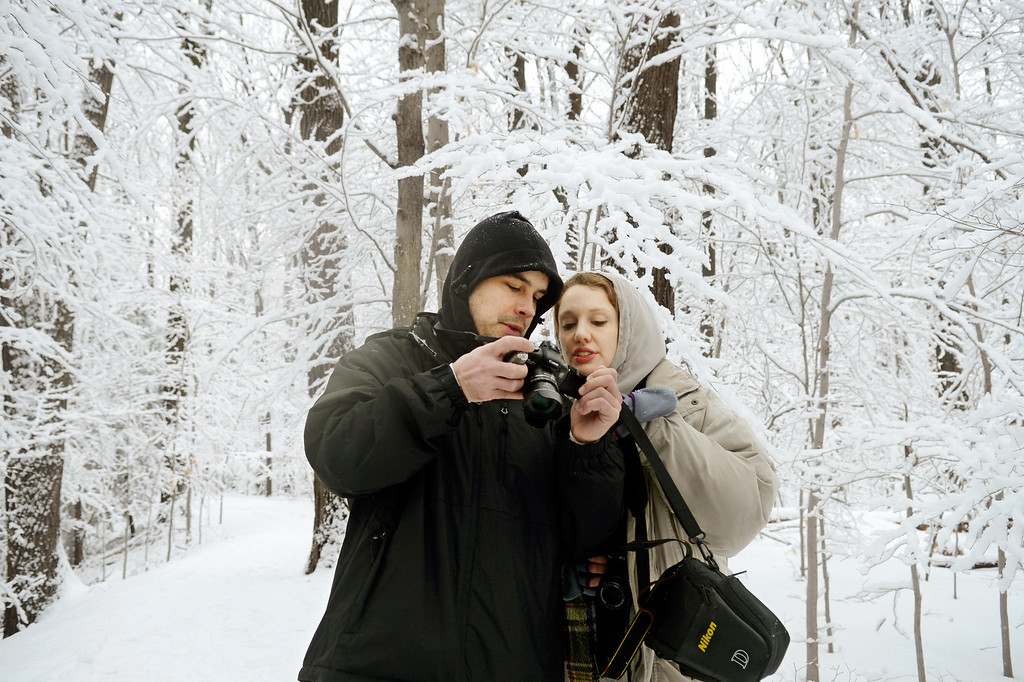. Maribeth Joeright/MJoeright@News-Herald.com Adam Dietrich, 30, of Willowick and Kate Mitchell, 29, of Kirtland look at photographs taken during a hike, Sunday at Penitentiary Glen in Kirtland. Saturday\'s rains eventually turned to snow which flocked all the trees, creating breathtaking scenery in every direction.