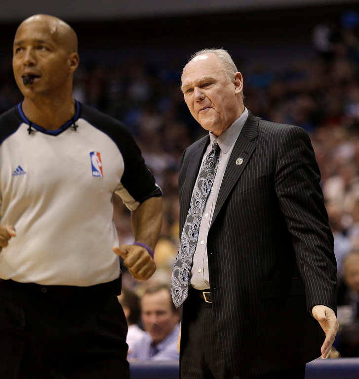 . Denver Nuggets head coach George Karl, right, questions a call during the first half of an NBA basketball game against the Dallas Mavericks, Friday, April 12, 2013, in Dallas. (AP Photo/LM Otero)