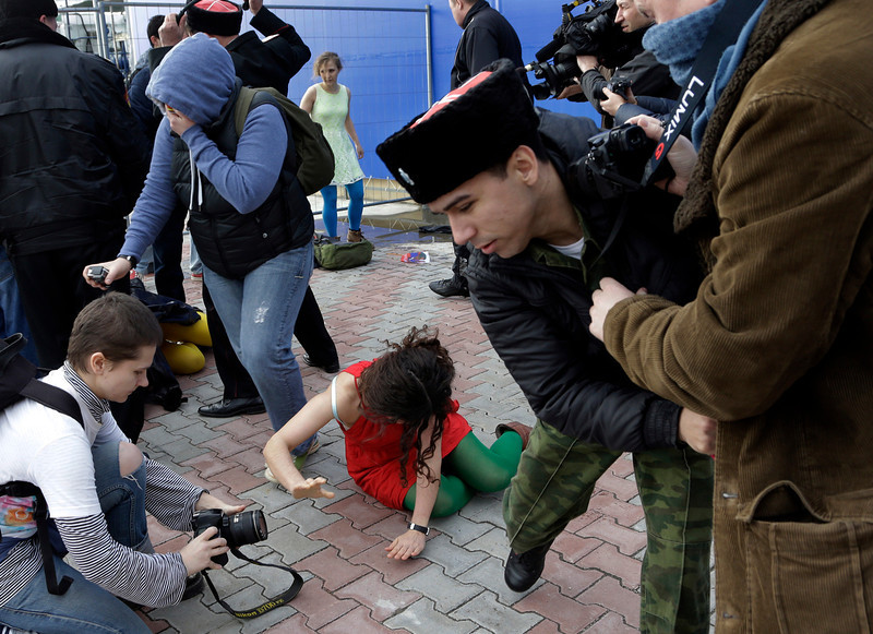 . A member of the punk group Pussy Riot lies on the ground as the group are attacked by Cossack militia in Sochi, Russia, on Wednesday, Feb. 19, 2014. The group had gathered to perform in a downtown Sochi restaurant, about 30km (21miles) from where the Winter Olympics are being held.They left the restaurant wearing bright dresses and ski masks and had only been performing for a few seconds when they were set upon by Cossacks.  (AP Photo/Morry Gash)