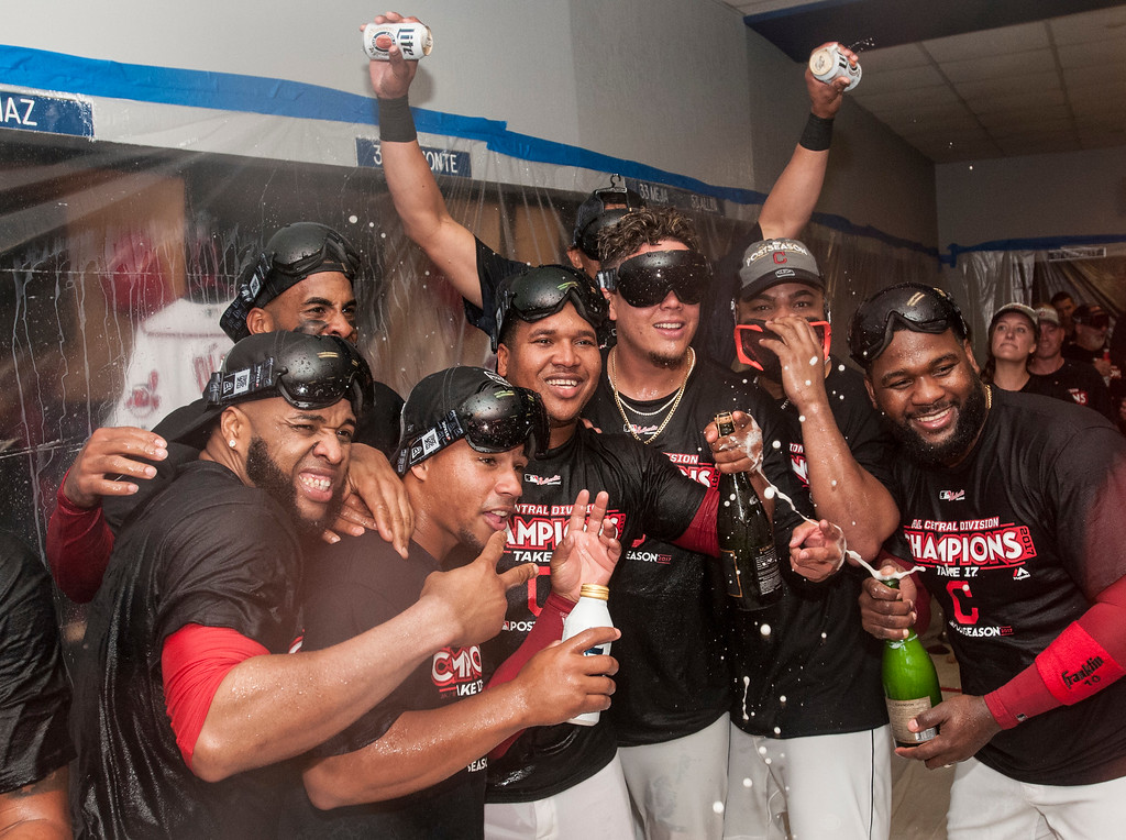 . Cleveland Indians\' Carlos Santana, left, Francisco Mejia, Jose Ramirez, Giovanny Urshela and Abraham Almonte, right, celebrate winning the American League Central Division and defeating the Kansas City Royals 3-2 after a baseball game in Cleveland, Sunday, Sept. 17, 2017. (AP Photo/Phil Long)