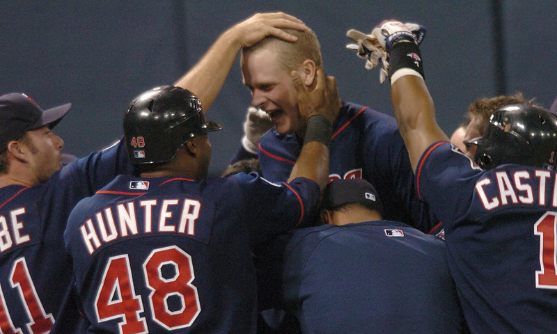 . Justin Morneau is mobbed by his teammates after hitting his second home run in the 10th inning to drive in three runs and beat the Chicago White Sox 7-4 on May 8, 2007.