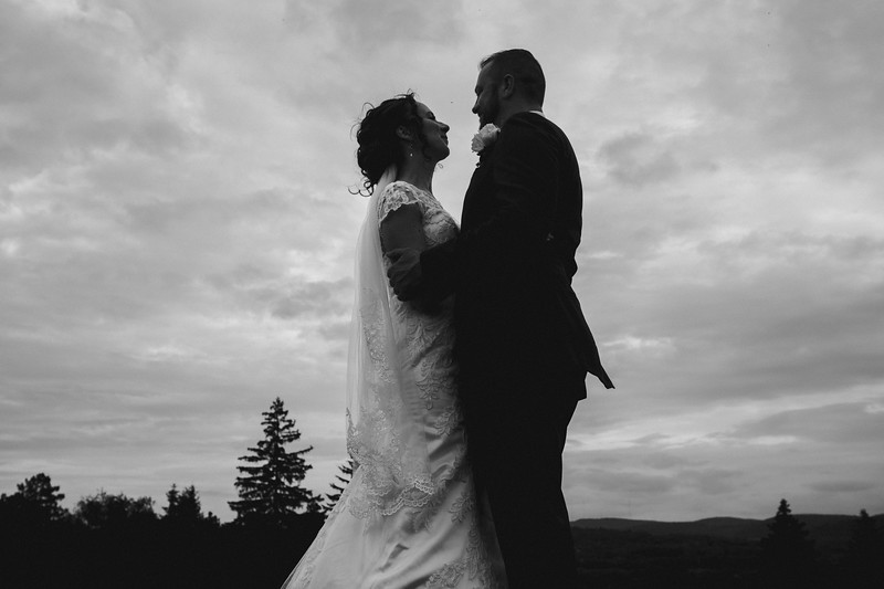 The bride and groom embracing against a dramatic sky.