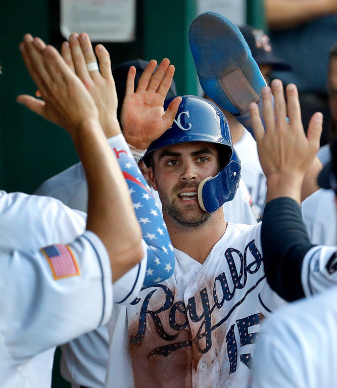. Kansas City Royals\' Whit Merrifield celebrates in the dugout after scoring on a double by Rosell Herrera during the second inning of a baseball game against the Cleveland Indians on Tuesday, July 3, 2018, in Kansas City, Mo. (AP Photo/Charlie Riedel)