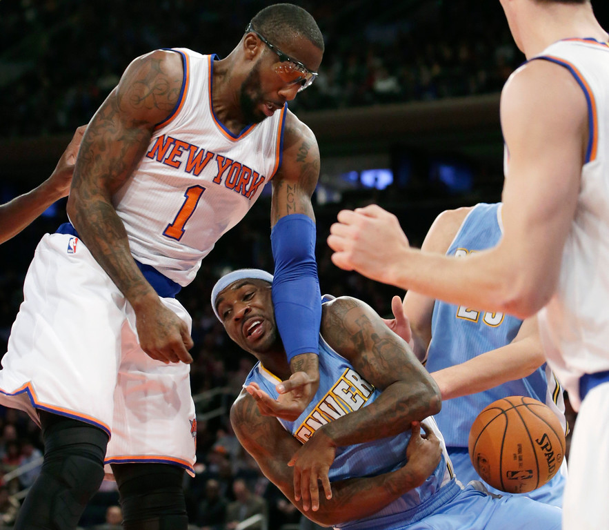 . New York Knicks forward Amar\'e Stoudemire (1) knocks the ball from the arms of Denver Nuggets guard Ty Lawson (3) in the first half of an NBA basketball game at Madison Square Garden in New York, Sunday, Nov. 16, 2014.  The Knicks defeated the Nuggets 109-93. (AP Photo/Kathy Willens)