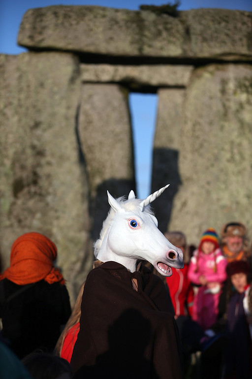 . A woman dressed as a unicorn watches the sun rise, as druids, pagans and revellers take part in a winter solstice ceremony at Stonehenge on December 21, 2012 in Wiltshire, England. Predictions that the world will end today as it marks the end of a 5,125-year-long cycle in the ancient Maya calendar, encouraged a larger than normal crowd to gather at the famous historic stone circle to celebrate the sunrise closest to the Winter Solstice, the shortest day of the year.  (Photo by Matt Cardy/Getty Images)