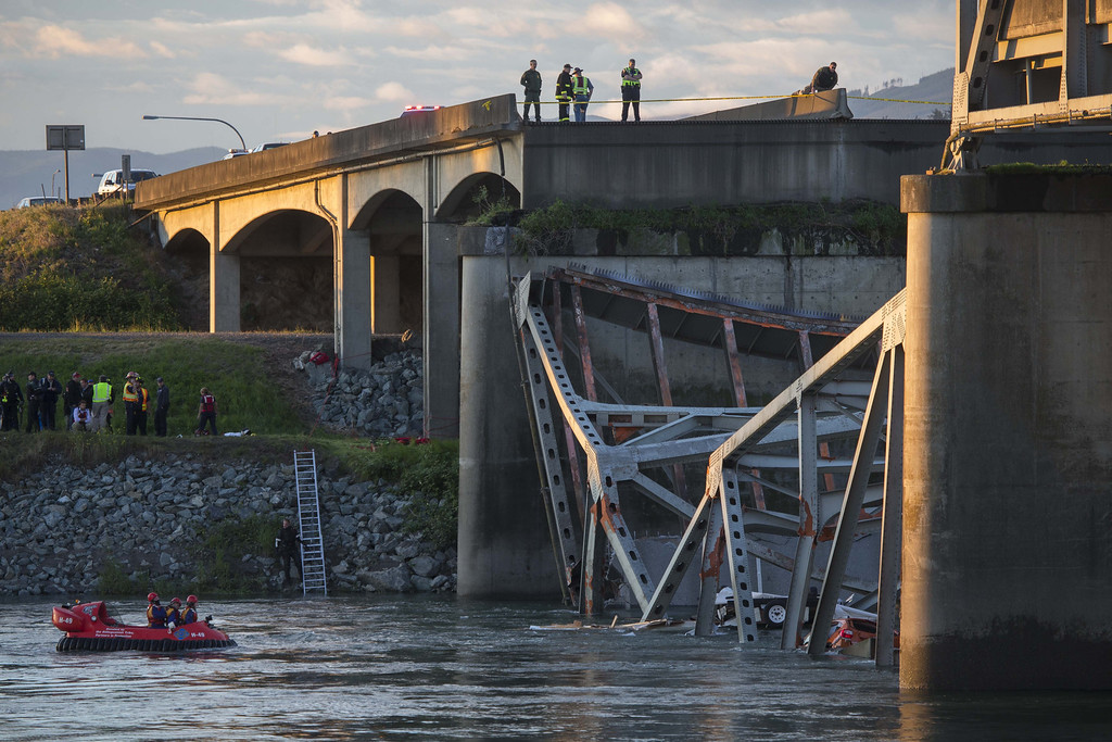 . A portion of the Interstate 5 bridge is submerged after it collapsed into the Skagit River dumping vehicles and people into the water as rescuers watch from the collapsed section of Interstate 5 and hovercraft search for survivors below in Mount Vernon, Wash., Thursday, May 23, 2013.  (AP Photo/The Seattle Times, Rick Lund)