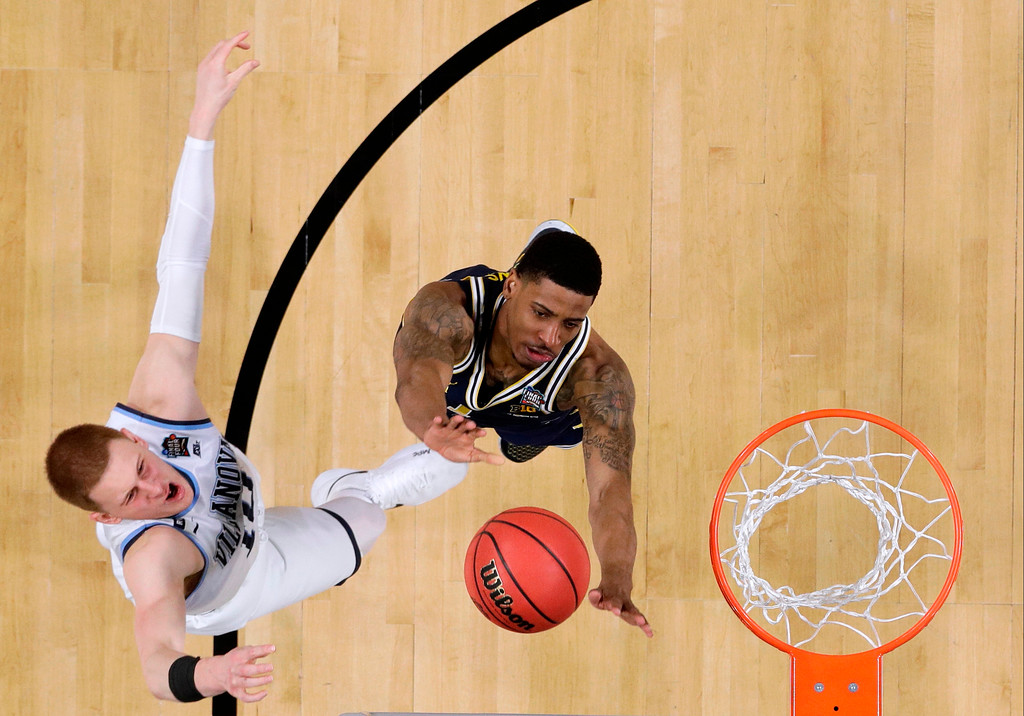 . Villanova guard Donte DiVincenzo, left, drives to the basket over Michigan guard Charles Matthews during the second half in the championship game of the Final Four NCAA college basketball tournament, Monday, April 2, 2018, in San Antonio. (AP Photo/David J. Phillip)