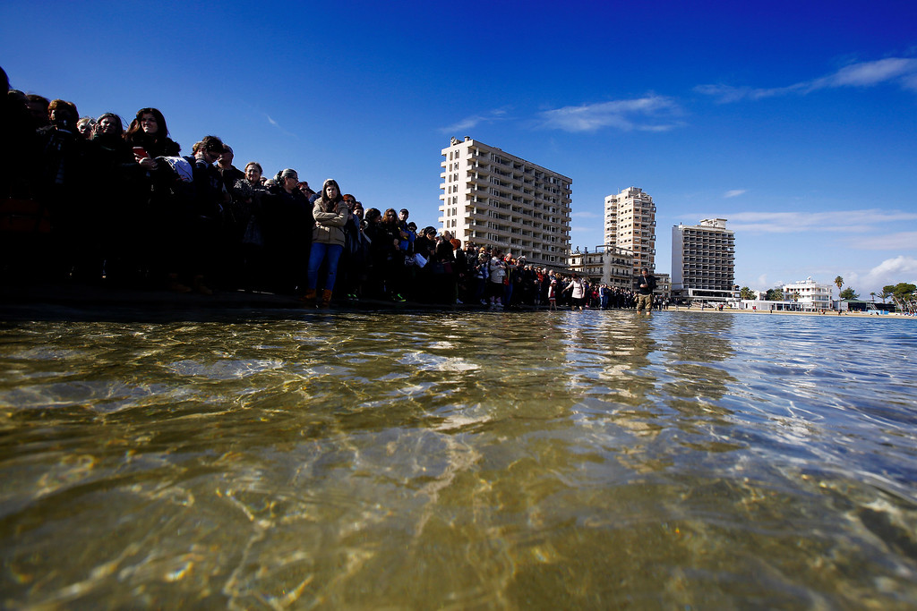 . Christians Orthodox Cypriot stand along the beach as during an epiphany ceremony to bless the sea waters at Famagousta or Varosia beach with the abandon hotels, are seen in the background, in the Turkish Cypriots breakaway north part of the divided island of Cyprus, Wednesday, Jan 6, 2016. More than 1,000 Orthodox Christian faithful attended the  Epiphany Day blessing of the waters in Famagusta in Cyprus�, the first time the ceremony has taken place since 1974 when the small island nation was cleaved along ethnic lines. (AP Photo/Petros Karadjias)