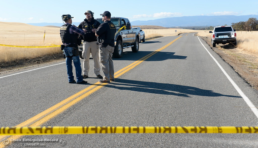 . Law enforcement officers stand near a truck that was involved along  Rancho Tehama Road following several shootings in Rancho Tehama California community Tues. Nov. 14, 2017.  (Bill Husa -- Enterprise-Record)