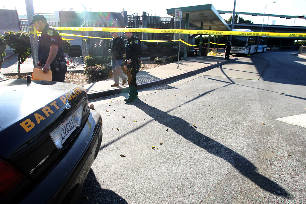 . A dead body covered, far right, lies on the sidewalk next to an AC Transit bus  as police investigate the fatal shooting in the bus yard outside the Bay Fair BART in San Leandro, Calif., on Saturday, Jan. 19, 2013. (Ray Chavez/Staff)