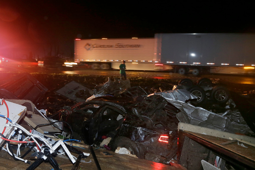 . A man walks past a wrecked automobile and RV on Interstate 40 in Mayflower, Ark., Sunday, April 27, 2014. A powerful storm system rumbled through the central and southern United States on Sunday, spawning a massive tornado. (AP Photo/Danny Johnston)