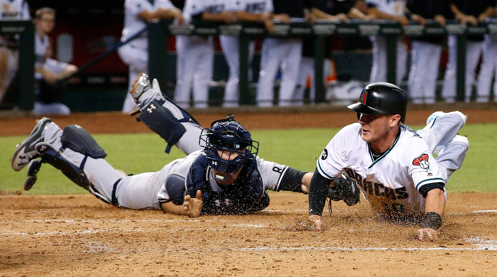 . Arizona Diamondbacks\' Chris Herrmann, right, scores a run ahead of the tag by New York Yankees\' Brian McCann, left, during the third inning of a baseball game Tuesday, May 17, 2016, in Phoenix. (AP Photo/Ross D. Franklin)
