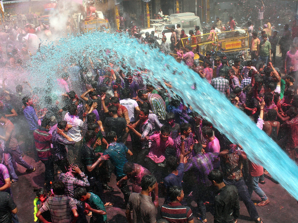 . Revelers dance as colorful water is sprinkled on them during a procession on the occasion of Holi, festival of colors in Bhopal, India, 17 March 2014. Holi is the Hindu spring festival of colors, celebrated with full zeal and fervor.  EPA/SANJEEV GUPTA