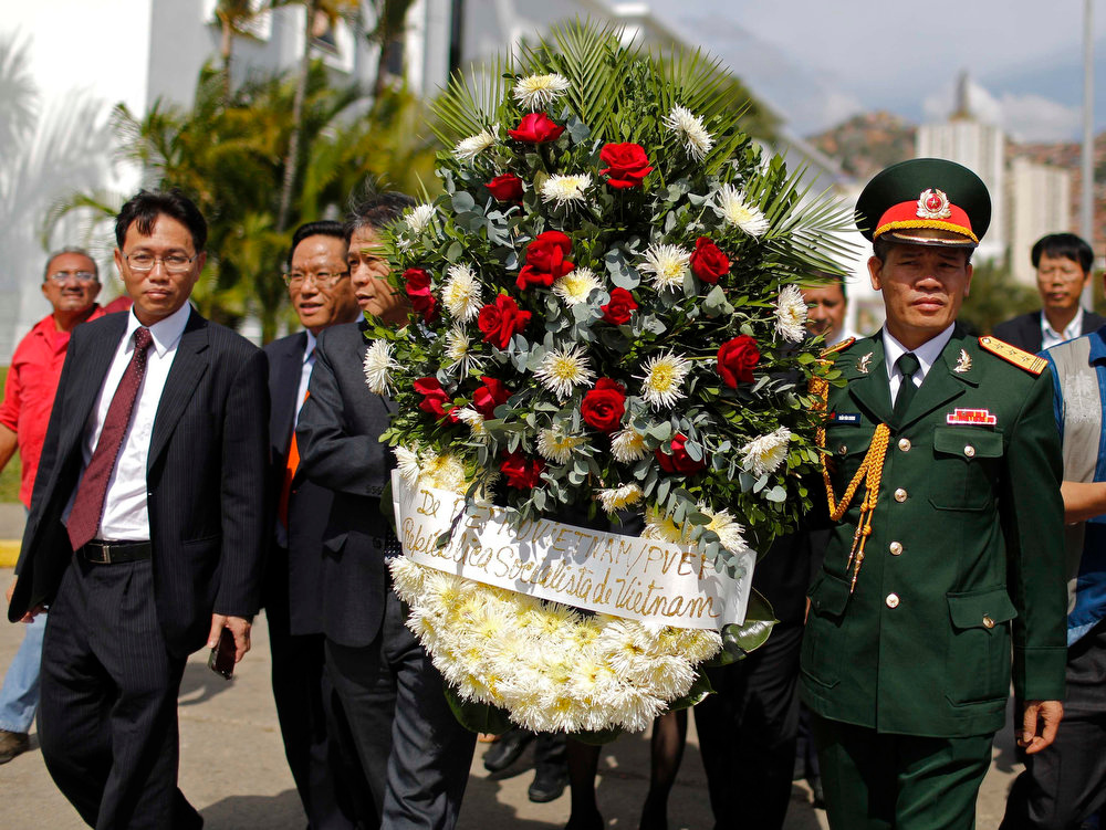 . An official delegation from Vietnam arrives with a wreath in tribute to Venezuela\'s late President Hugo Chavez as his body lies in state at the Military Academy in Caracas on March 7, 2013. Venezuelans flocked to pay tribute to Chavez two days after he died of cancer.    REUTERS/Tomas Bravo