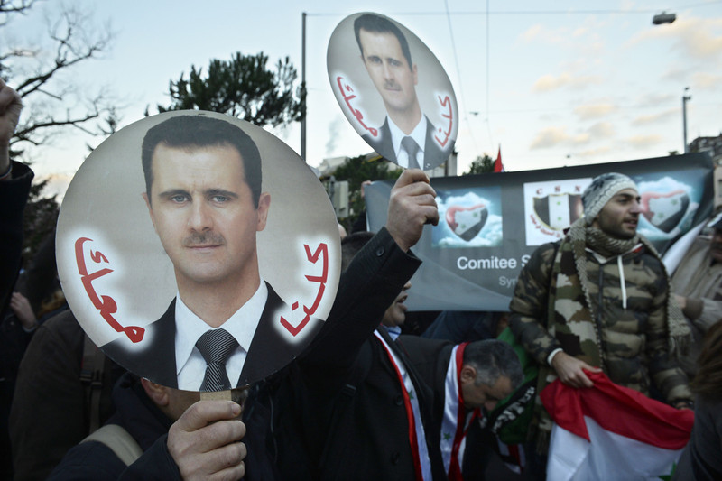 . Syrian pro government supporters hold pictures of Syrian president Bashar al-Assad as they demonstrate during the so-called Geneva II peace talks on January 22, 2014 in Montreux. Representatives of Syrian President Bashar al-Assad, a deeply divided opposition, world powers and regional bodies started a long-delayed peace conference aimed at bringing an end to a nearly three-year civil war. (PHILIPPE DESMAZES/AFP/Getty Images)