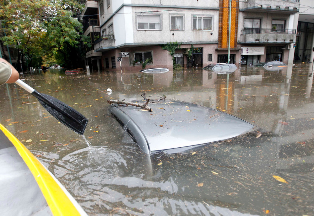 . Submerged cars are seen in a flooded street after a rainstorm in Buenos Aires April 2, 2013. Thunderstorms damaged property and vehicles, cut power and caused delays on flights in Buenos Aires and its suburbs. The City\'s SAME emergency service announced that the death toll has risen to five.     REUTERS/Enrique Marcarian