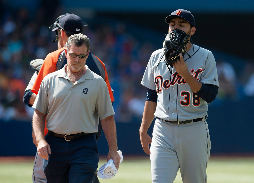 . Detroit Tigers relief pitcher Joakim Soria, right, walks off the field with a team trainer in the tenth inning of a baseball game against the Toronto Blue jays, Saturday, Aug. 9, 2014 in Toronto. The Blue Jays defeated the Tigers 3-2. (AP Photo/The Canadian Press, Darren Calabrese)