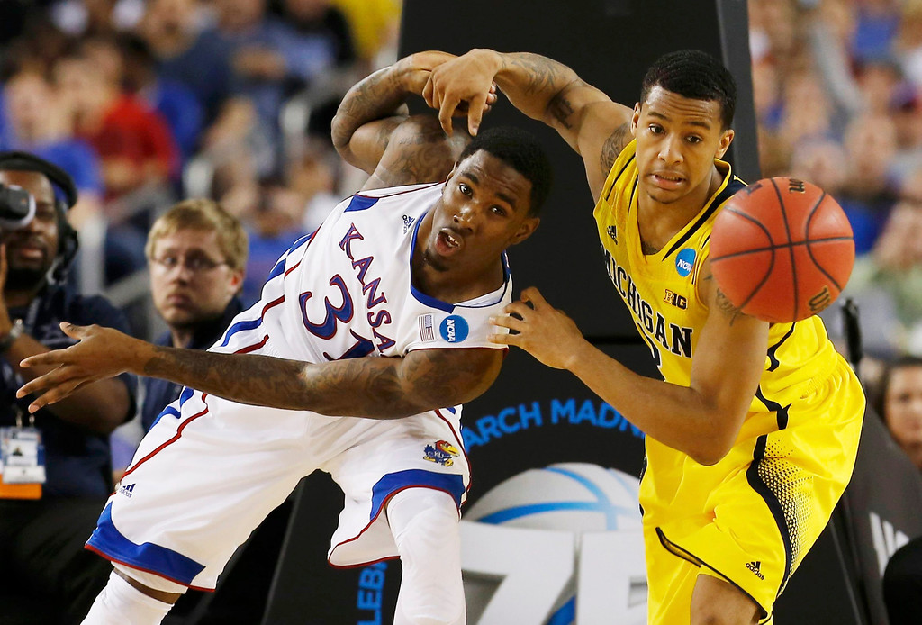 . Kansas Jayhawks forward Jamari Traylor (L) and Michigan Wolverines guard Trey Burke battle for a rebound during the second half in their South Regional NCAA men\'s basketball game in Arlington, Texas March 29, 2013. REUTERS/Jim Young