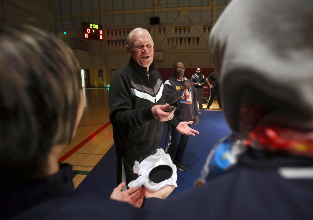 . Albany High School wrestling coach Kermit Bankson, center, receives a whistle from co-captains Chanel Chawa, left, and Jesse Chua, right, before his team competes against Tennyson High School at Albany High School in Albany, Calif. on Friday, Jan. 17, 2013.  (Jane Tyska/Staff)