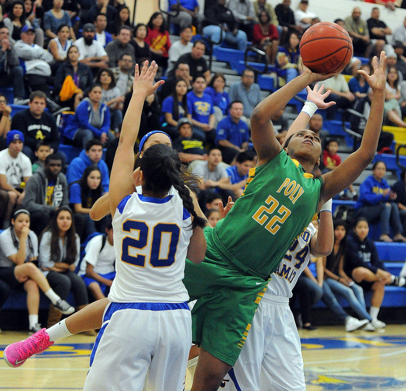 . Long Beach Poly\'s Jada Matthews (22) drives to the basket past Bishop Amat\'s Janae Chamois (20) in the first half of a CIF State Southern California Regional semifinal basketball game at Bishop Amat High School on Tuesday, March 12, 2013 in La Puente, Calif. Long Beach Poly won 52-34.  (Keith Birmingham Pasadena Star-News)