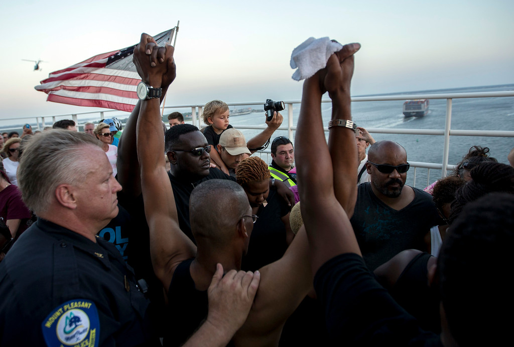 . People raise their hands as a show of unity as thousands of marchers meet in the middle of Charleston\'s main bridge after nine black church parishioners were gunned down during a Bible study, Sunday, June 21, 2015, in Charleston, S.C.  (AP Photo/Stephen B. Morton)
