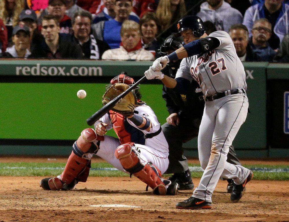 . Detroit Tigers\' Jhonny Peralta hits a double in front of Boston Red Sox catcher David Ross off Red Sox relief pitcher Craig Breslow in the eighth inning during Game 1 of the American League baseball championship series Saturday, Oct. 12, 2013, in Boston. (AP Photo/Charlie Riedel)