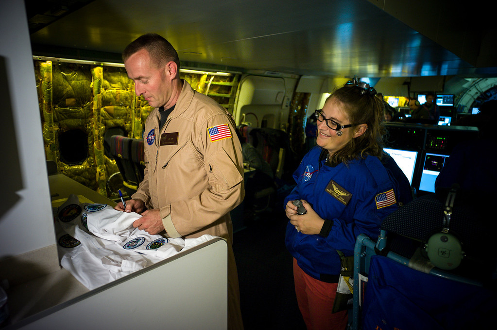 . Megan Tucker, teacher at Palmdale Aerospace Academy gets pilot Jim Less to sign her lab coat during an overnight science flight on the modified 747SP jet over the US.    (Photo by David Crane/Los Angeles Daily News)