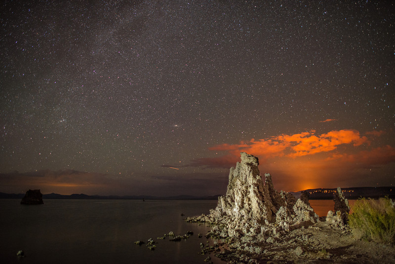 A fire rages in the forest behind mono lake, illuminating the night sky in orange.