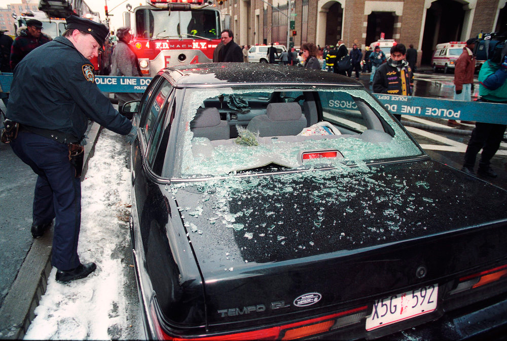 Description of . A police officer surveys blast damage to a car in front of the World Trade Center after a blast ripped through the world's second tallest office complex, killing six people and injuring more than 1,000 people in New York on February 26, 1993. The Port Authority of New York and New Jersey will commemorate the 20th anniversary of the 1993 World Trade Center bombing on February 26, with a tribute to the six victims and an unborn child who lost their lives during the attack. REUTERS/Mike Segar