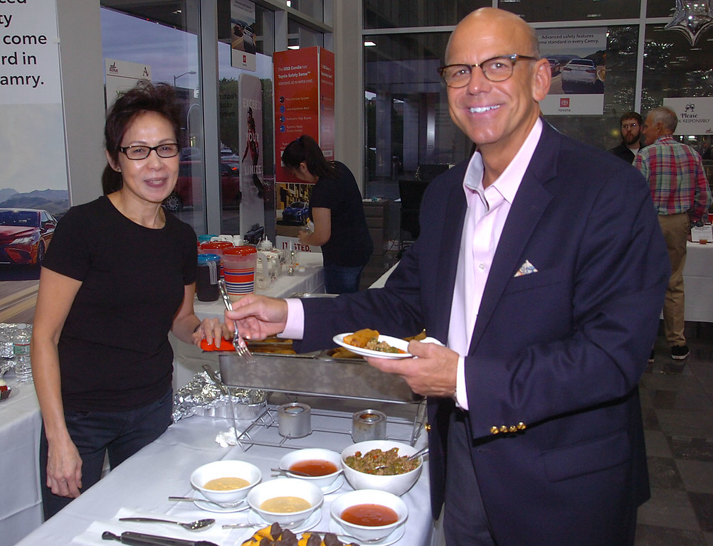 . Carine Wong of Hunan serves Rodger McKinney of Ardmore veggie egg rolls  with sausages and pepper at Ardmore Initiatives\' \'A Taste of Ardmore\' recently.