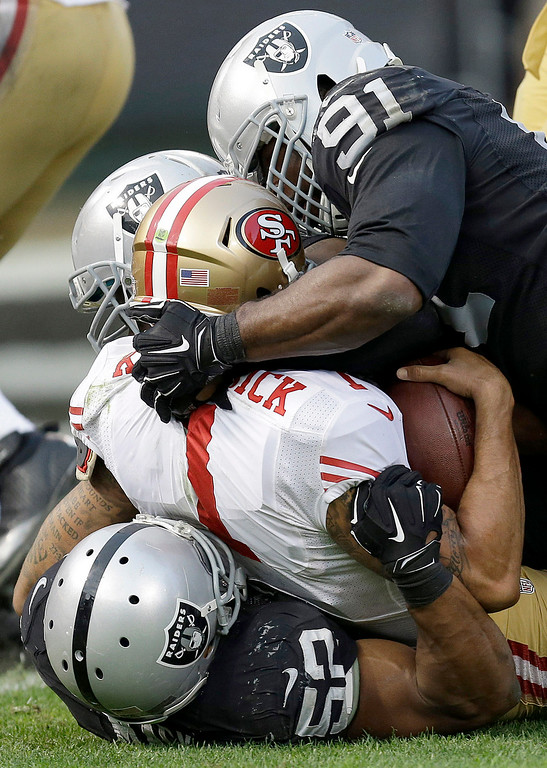 . San Francisco 49ers quarterback Colin Kaepernick, center, is sacked by Oakland Raiders outside linebacker Khalil Mack, bottom, as defensive end Justin Tuck (91) converges during the fourth quarter of an NFL football game in Oakland, Calif., Sunday, Dec. 7, 2014. The Raiders won 24-13. (AP Photo/Ben Margot)