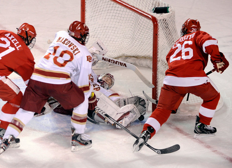 . Denver goalie Juho Olkinuora (31) made a save in the first period as Cornell wing John Esposito (26) looked for a rebound. The University of Denver hockey team hosted Cornell at Magness Arena Saturday night, January 5, 2013. Karl Gehring/The Denver Post