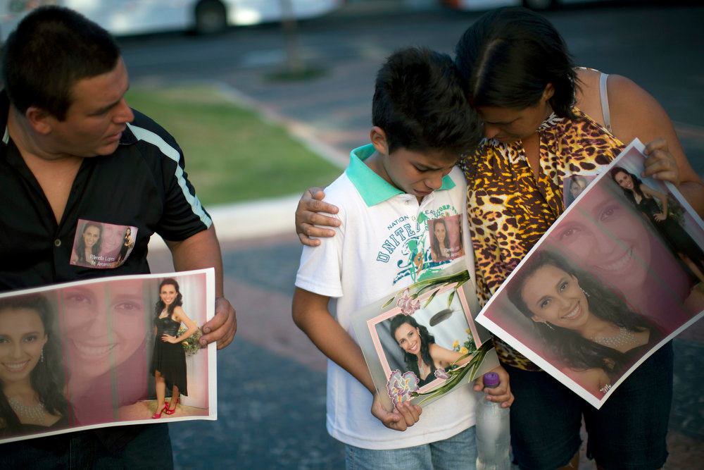 Description of . Relatives hold photographs of Pamella Lopes, who died in a nightclub fire, as they stand a public square near the nightclub in Santa Maria, Brazil, Monday, Jan. 28, 2013. A fast-moving fire roared through the crowded, windowless Kiss nightclub in this southern Brazilian city early Sunday, killing more than 230 people. Many of the victims were under 20 years old, including some minors. (AP Photo/Felipe Dana)