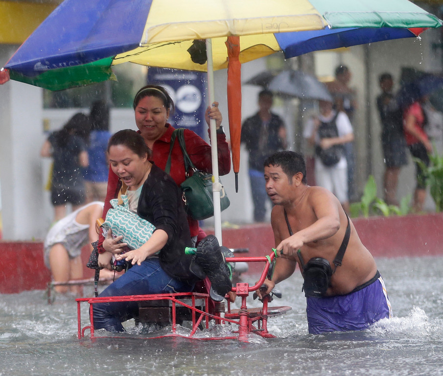 ". Commuters are ferried on a three-wheeled tricycle locally known as ""sidecar\"" after heavy monsoon rains spawned by tropical storm Fung-Wong flooded Manila and most parts of the metropolis Friday, Sept 19, 2014 in the Philippines.(AP Photo/Bullit Marquez)"
