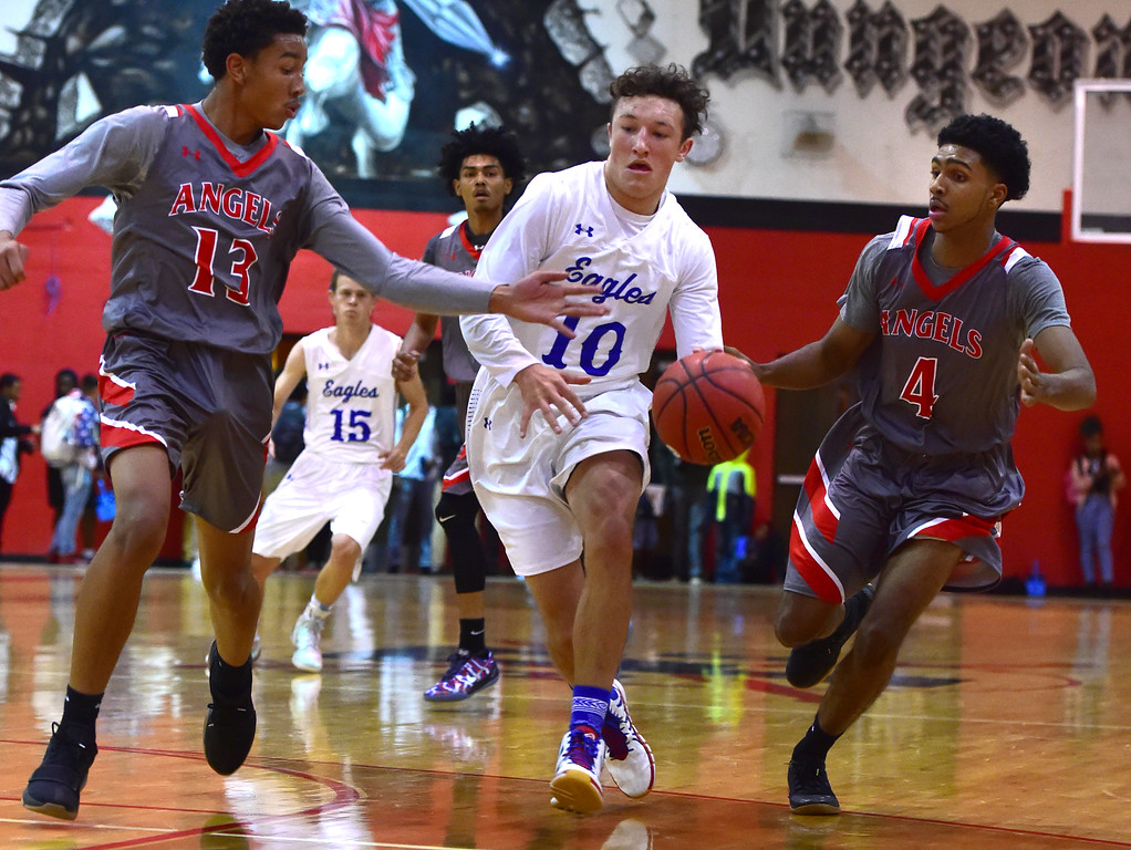 . Broomfield High School\'s Steven Croell between Denver East\'s Clayton Finley-Ponds and Ja\'Shawn Chisel during their game in the Fairview Festival on Wednesday. For More photos go to bocopreps.com Paul Aiken Staff Photographer Dec 6 2017