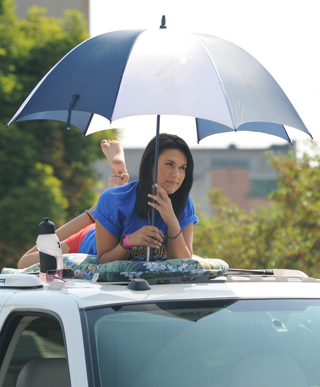 . Kristy Willauer, age 15, of Macomb Township, Mich., keeps cool under an umbrella on top of her family\'s vehicle, as she watches the Dream Cruise, Saturday, August 15, 2009, in Pontiac, Mich.  (The Oakland Press/Jose Juarez)
