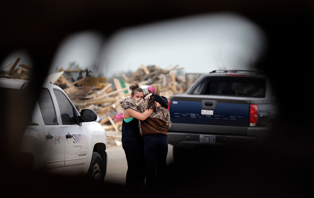 . Friends, seen through debris, comfort each other at the site of a a home destroyed by Sunday\'s tornado, Tuesday, April 29, 2014, in Vilonia, Ark.  (AP Photo/Eric Gay)