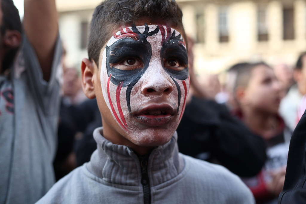 . An Egyptian youth wears face paint at a demonstration outside the country\'s high court in Cairo, Egypt, Saturday, April 6, 2013. Thousands of activists took to the streets Saturday to mark the fifth anniversary of the founding of a leading opposition group, the April 6 Youth Movement, and to push a long list of demands on Morsi, including the formation of a more inclusive government amid a worsening economy.(AP Photo/Ariana Drehsler)