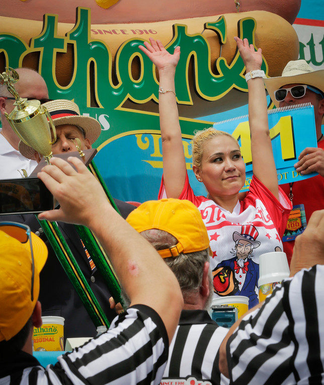 . Miki Sudo, right, celebrates after winning the women\'s division of the Nathan\'s Famous Hot Dog Eating Contest on Tuesday, July 4, 2017, in the Brooklyn borough of New York. The Las Vegas woman ate 41 hot dogs and buns in 10 minutes to win her fourth straight title. (AP Photo/Bebeto Matthews)