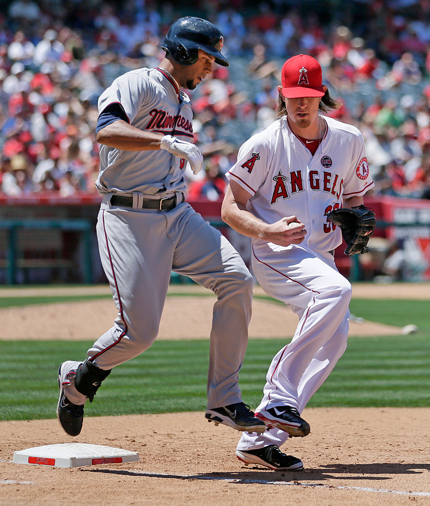 . Minnesota\'s Aaron Hicks, left, is forced out at first base by Angels starter Jered Weaver during the sixth inning. (AP Photo/Jae C. Hong)